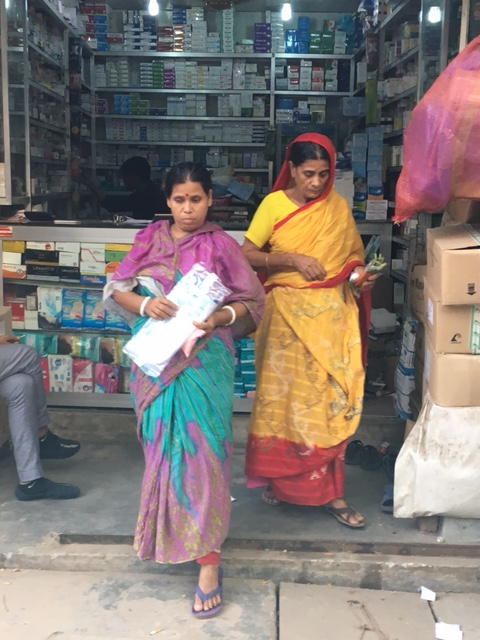 Two women purchase chemotherapy drugs at a pharmacy outside the hospital